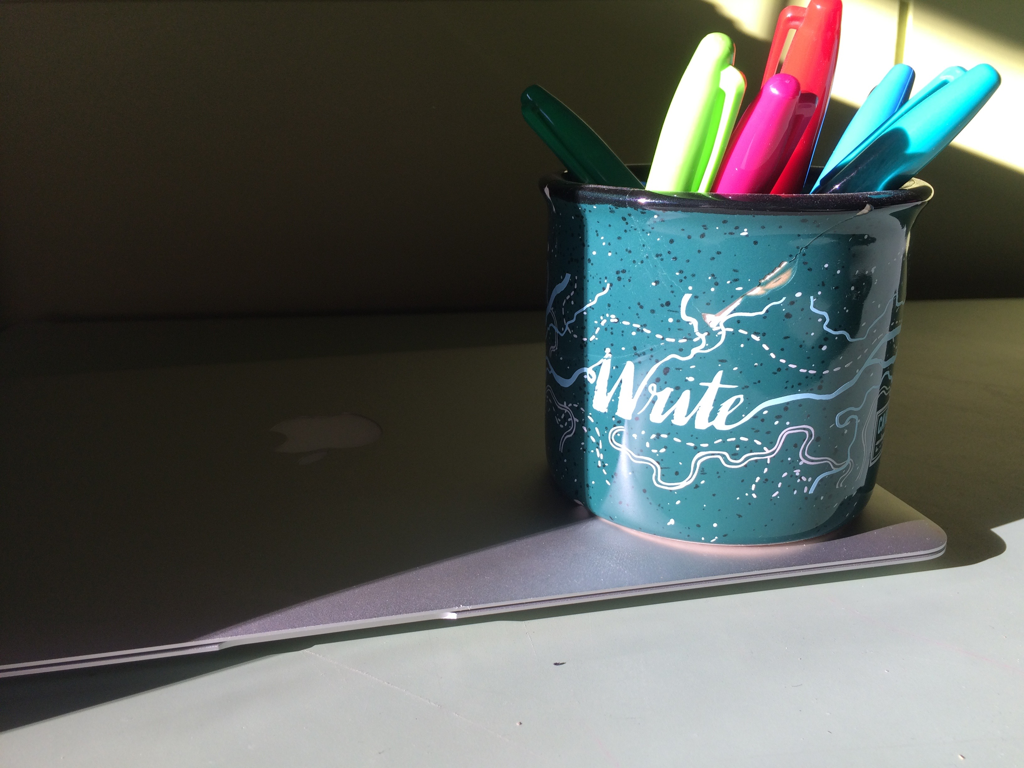 markers in a mug on top of laptop