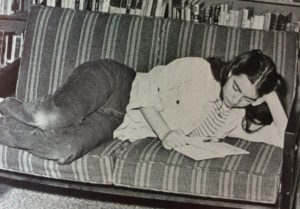 teen Mabel reading on a couch in library